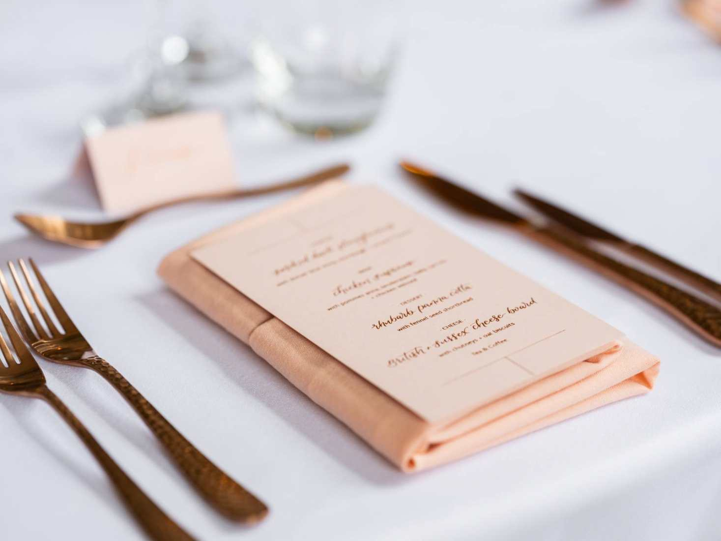 A place setting with copper cutlery and a menu