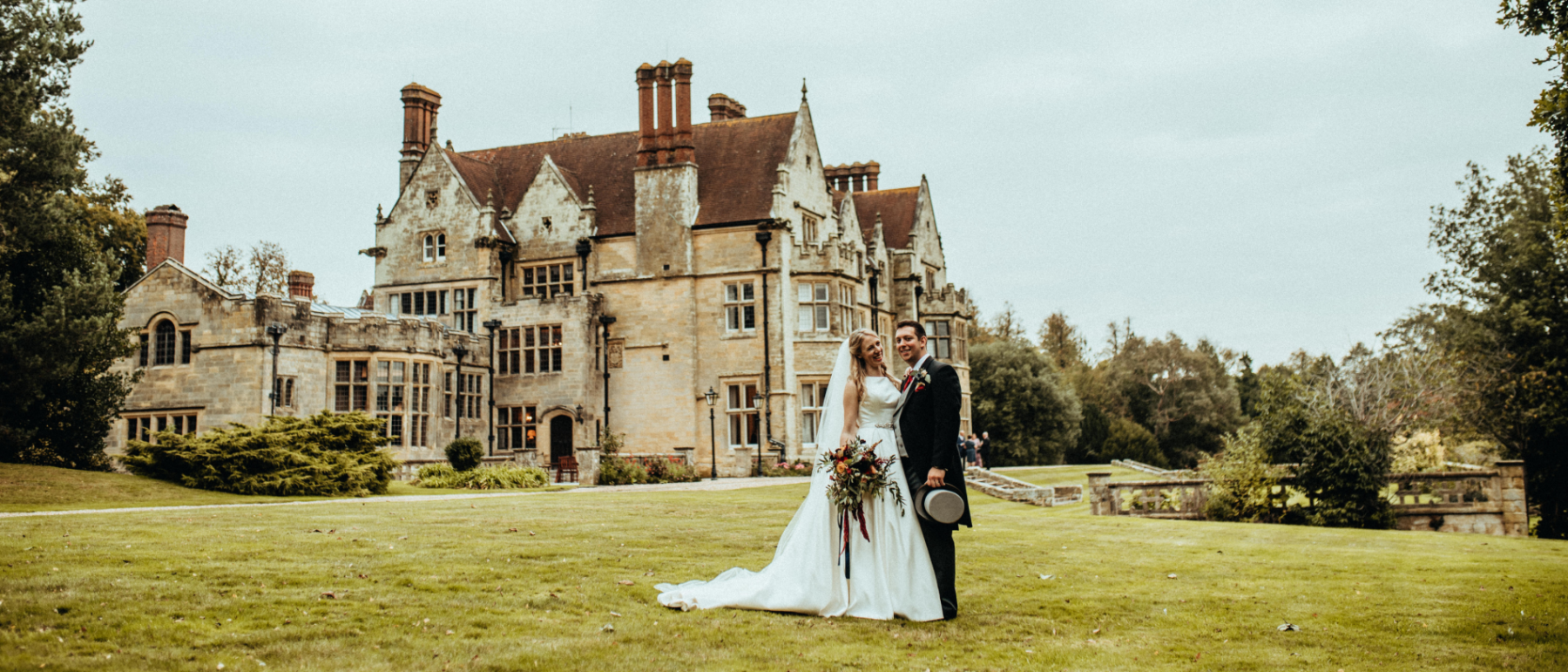 A Bride & Groom stand in front of Balcombe Place